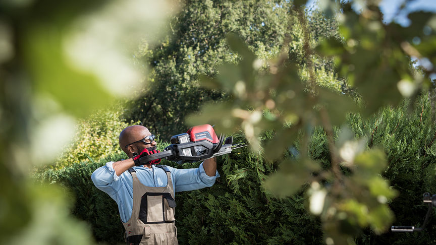Model holding Honda's cordless hedge trimmer in a garden.