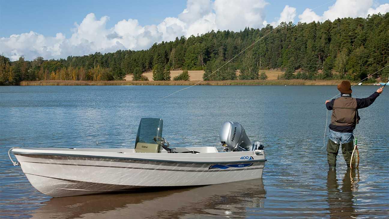 Man aan het vissen naast een kleine boot met een Honda buitenboordmotor
