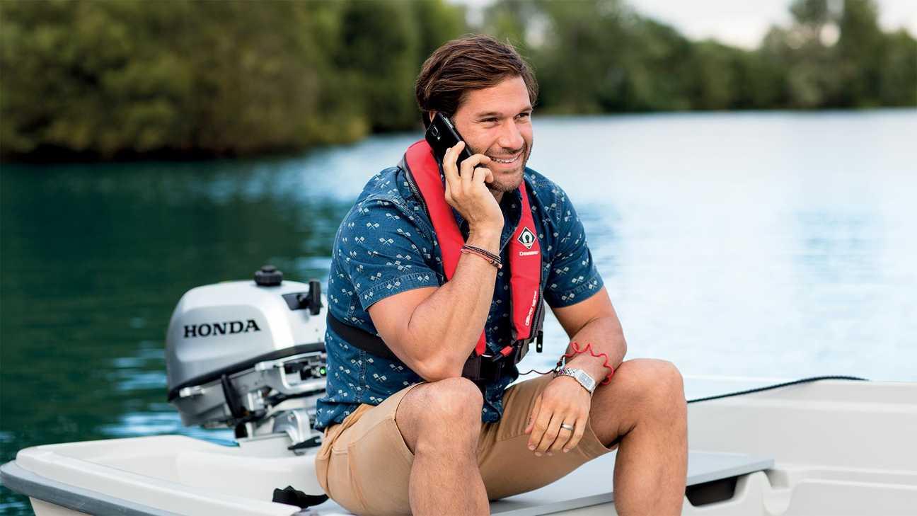 Man op kleine boot die zijn telefoon oplaadt via de buitenboordmotor tijdens het praten