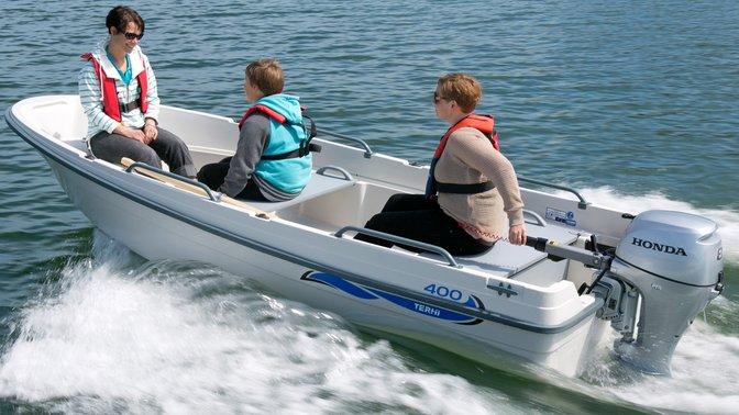 Boot met Honda motor, in gebruik door modellen, kustlocatie.